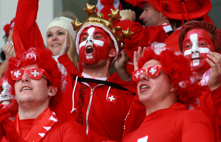 Switzerland football team fans with their country color dress